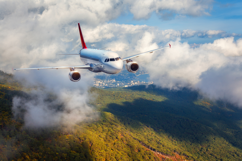 Airplane is flying in clouds over mountains with forest at sunset. Landscape with white passenger airplane, cloudy sky and green trees. Passenger aircraft is landing. Business travel. Commercial plane