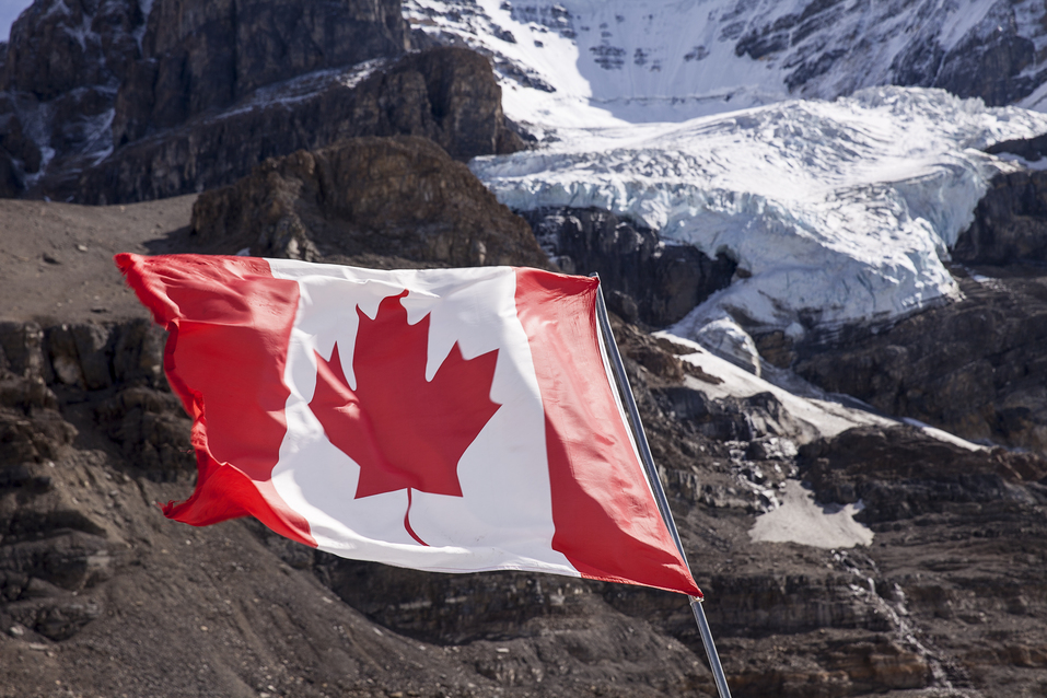 The maple leaf of the Canadian Flag flutters in a brisk wind. In the background, the main glacier of Mount Andromeda tumbles from the summit headwall.